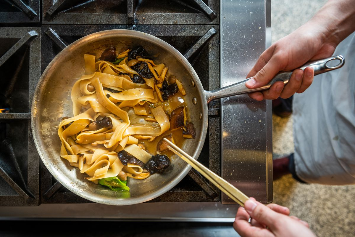 Japanese mushroom pappardelle with shishito peppers in a nonstick pan.