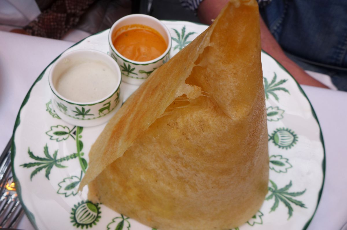 A brownish flatbread cone sided with two small dishes of sauce. one cream colored, one pinkish brown.