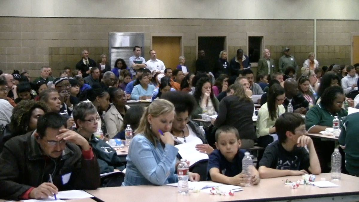 Community members, parents, students and teachers crowd the cafeteria at Martin Luther King Junior Early College to hear more about the reform plan.