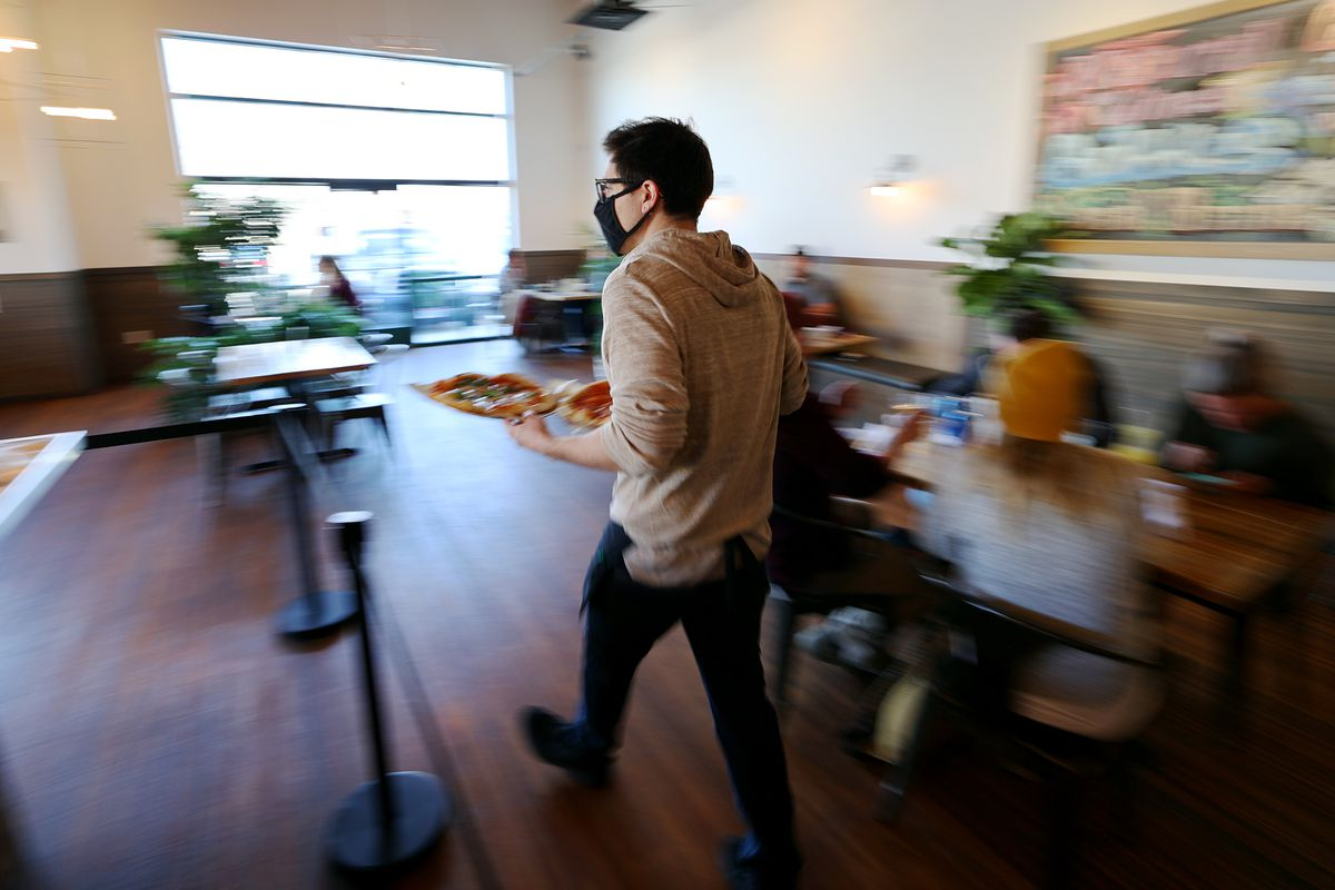 Server Shade Hammand takes an order out to a table at Oak Wood Fire Kitchen in Draper on Tuesday, Dec. 8, 2020.