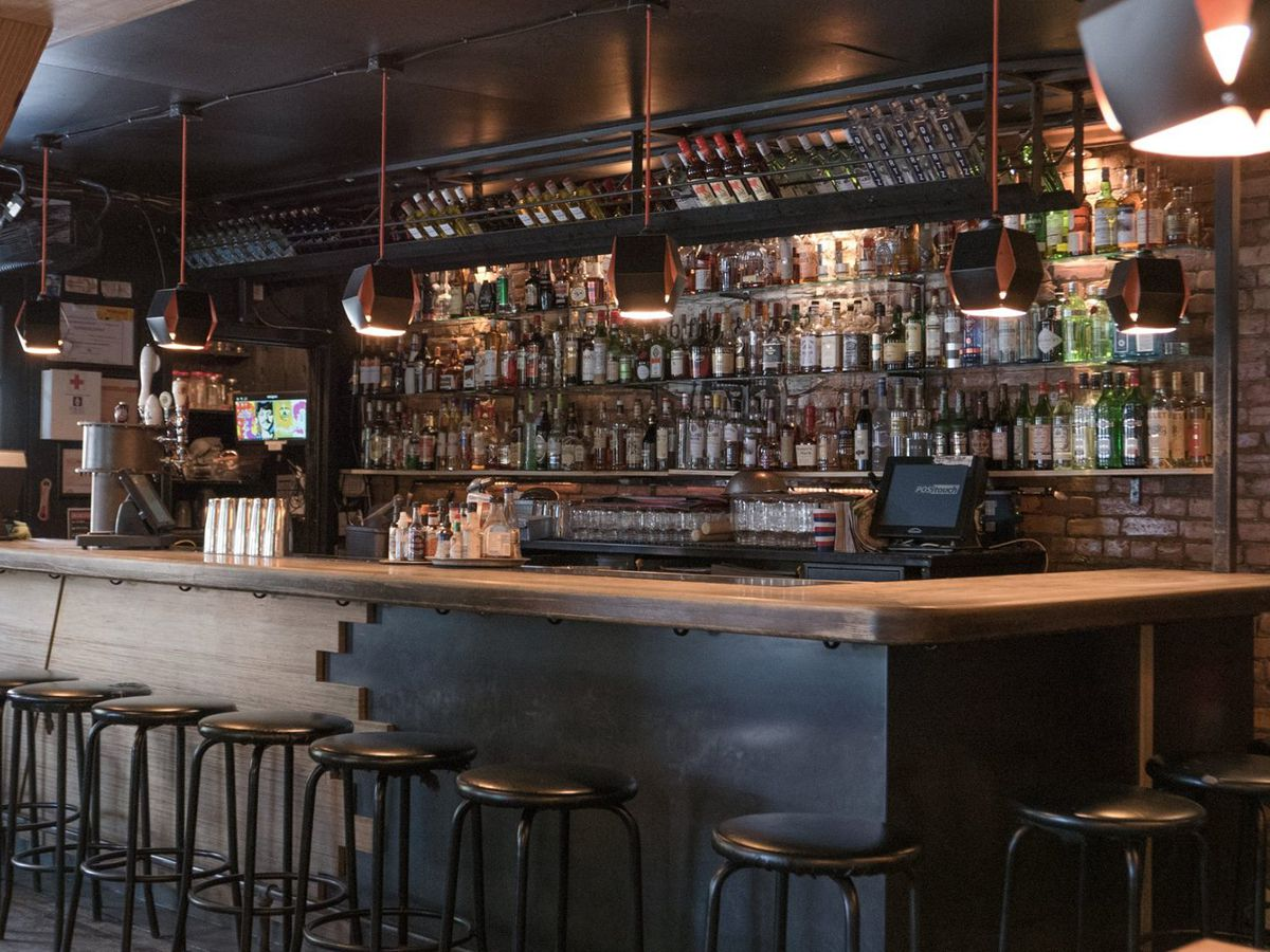 A empty bar with shelves behind it lined with alcohol bottles.