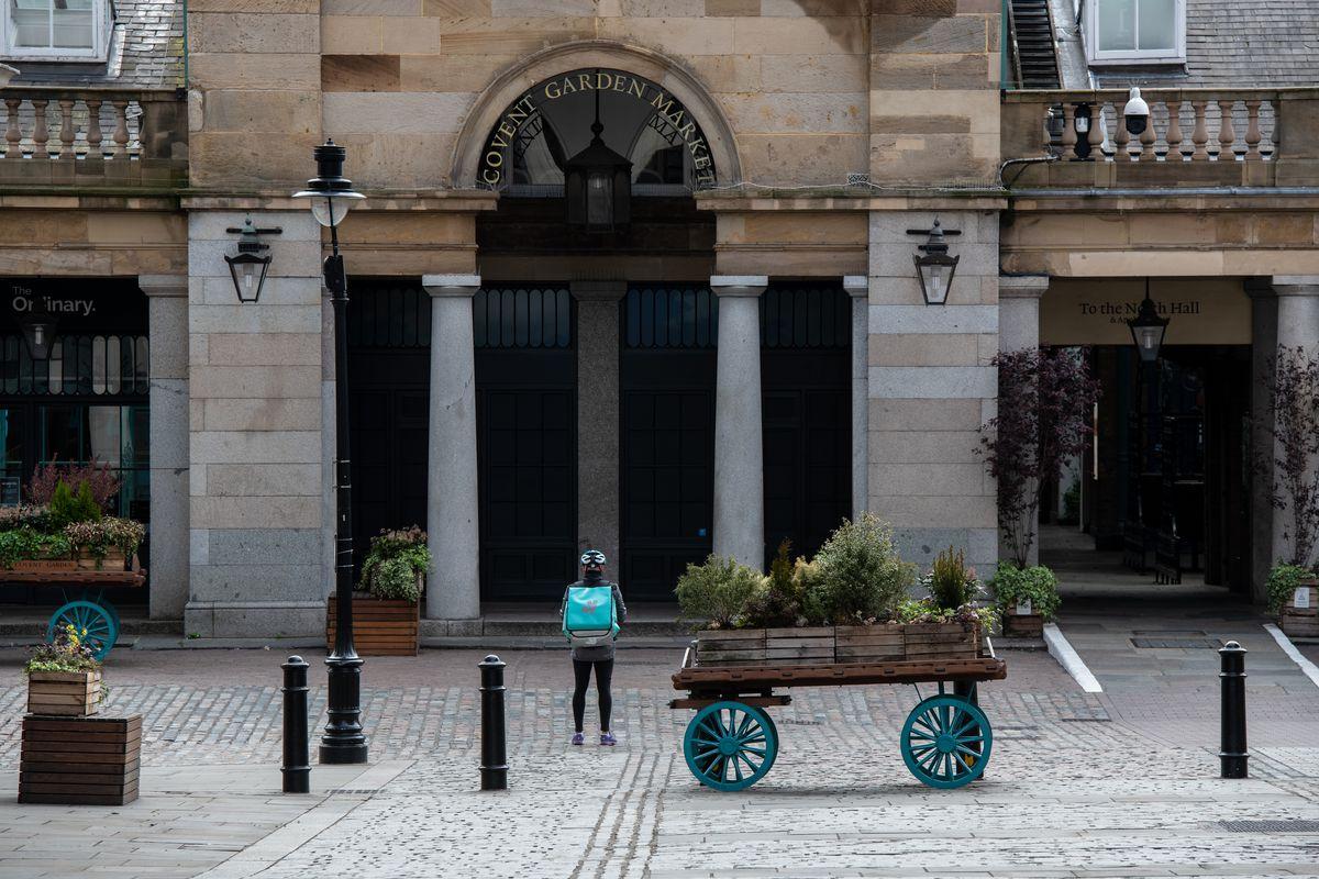 Deliveroo rider stands outside London restaurant neighbourhood Covent Garden during coronavirus lockdown