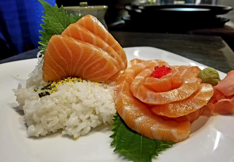 About six pieces of salmon sushi, three fanned out in a rose-like pattern