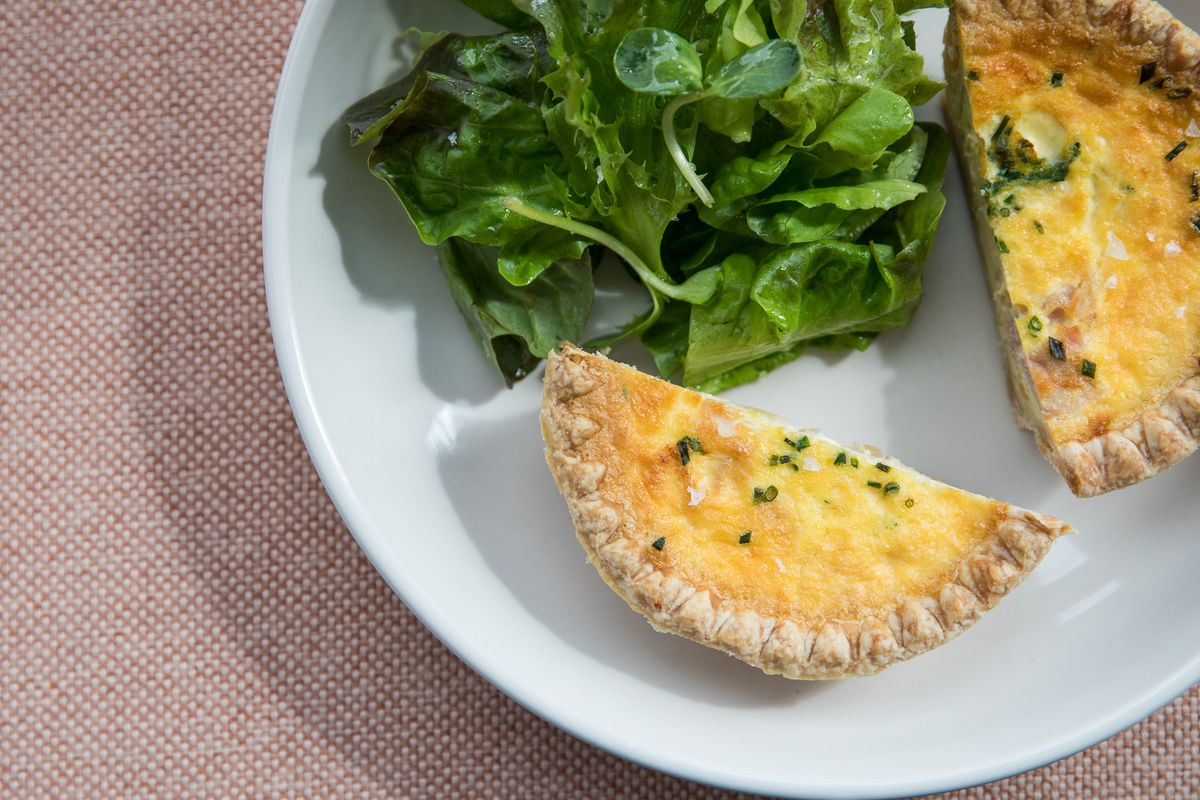 Quiche sliced in half on a white plate with green salad.