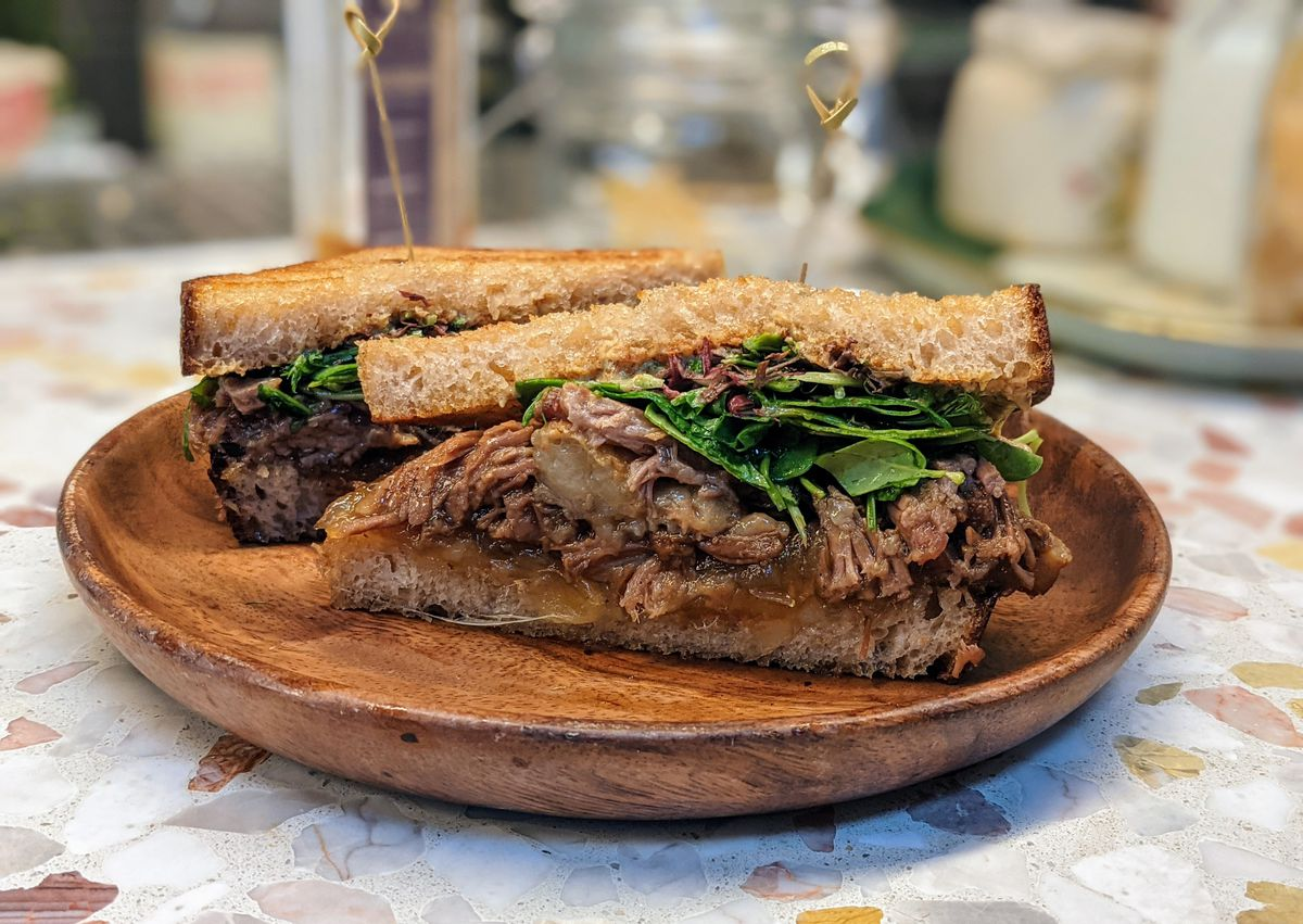 Brisket sandwich with raclette and arugula on sourdough bread at Agnes in Pasadena.