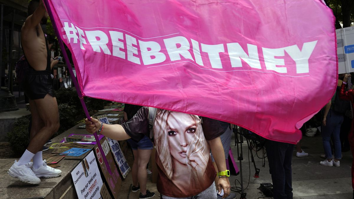 """A Britney Spears supporter waves a """"Free Britney"""" flag outside of a court hearing concerning the pop singer's conservatorship."""
