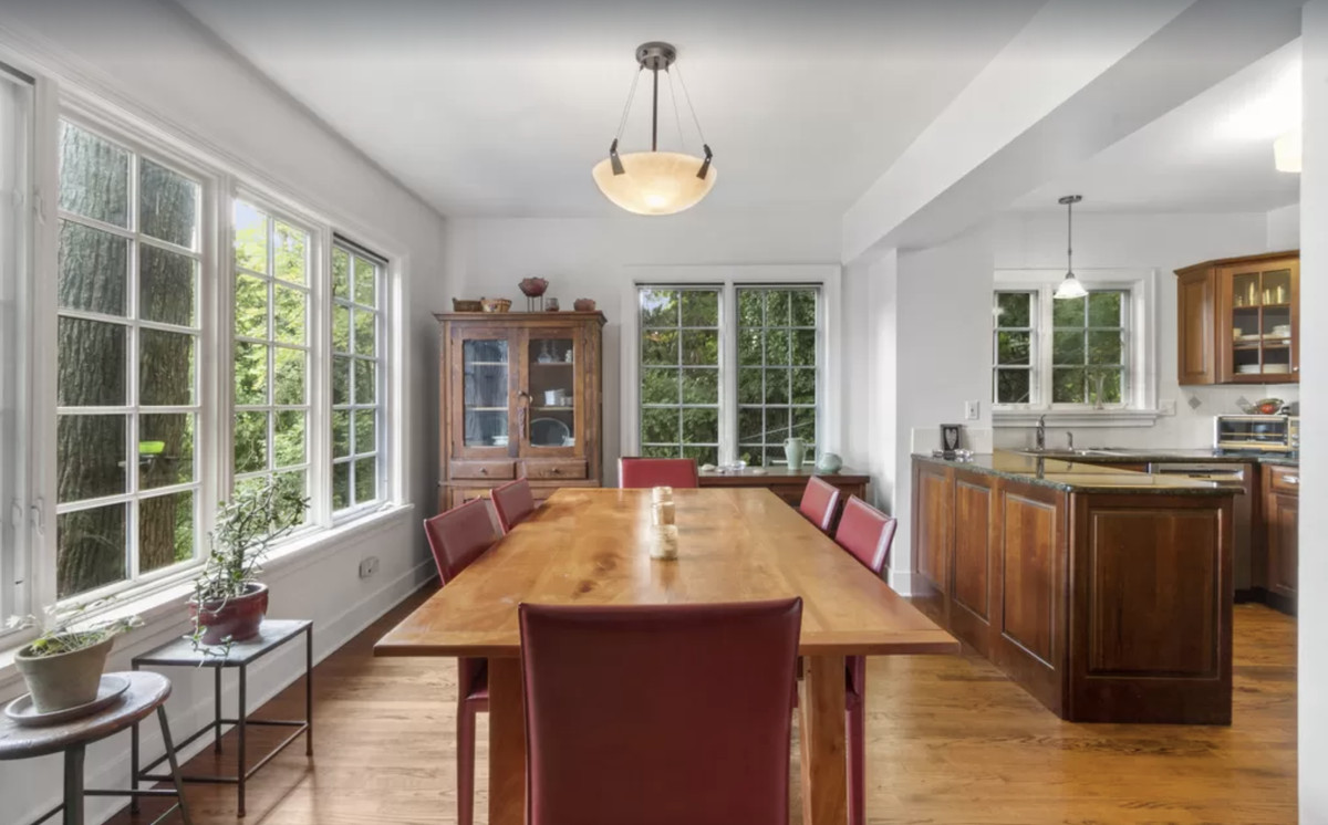 An open kitchen and dining area surrounded by paned windows with views of trees.