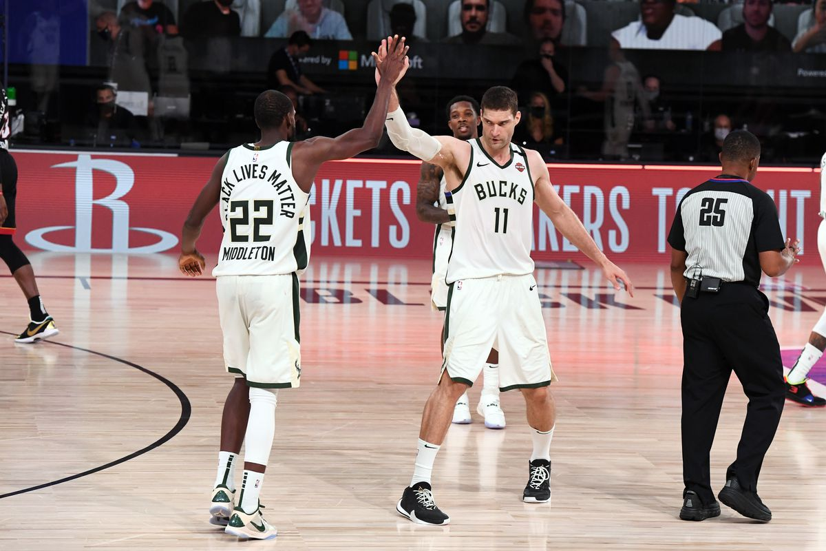 Khris Middleton of the Milwaukee Bucks and Brook Lopez of the Milwaukee Bucks high five during Game Four of the Eastern Conference Semifinals of the NBA Playoffs on September 6, 2020 at The AdventHealth Arena at ESPN Wide World Of Sports Complex in Orlando, Florida.