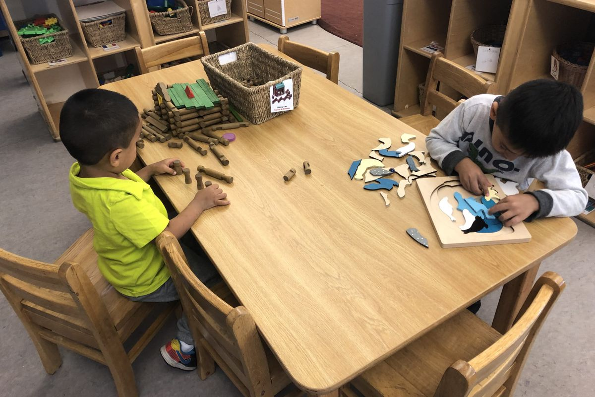 Two preschool children work at a puzzle table in Chicago.