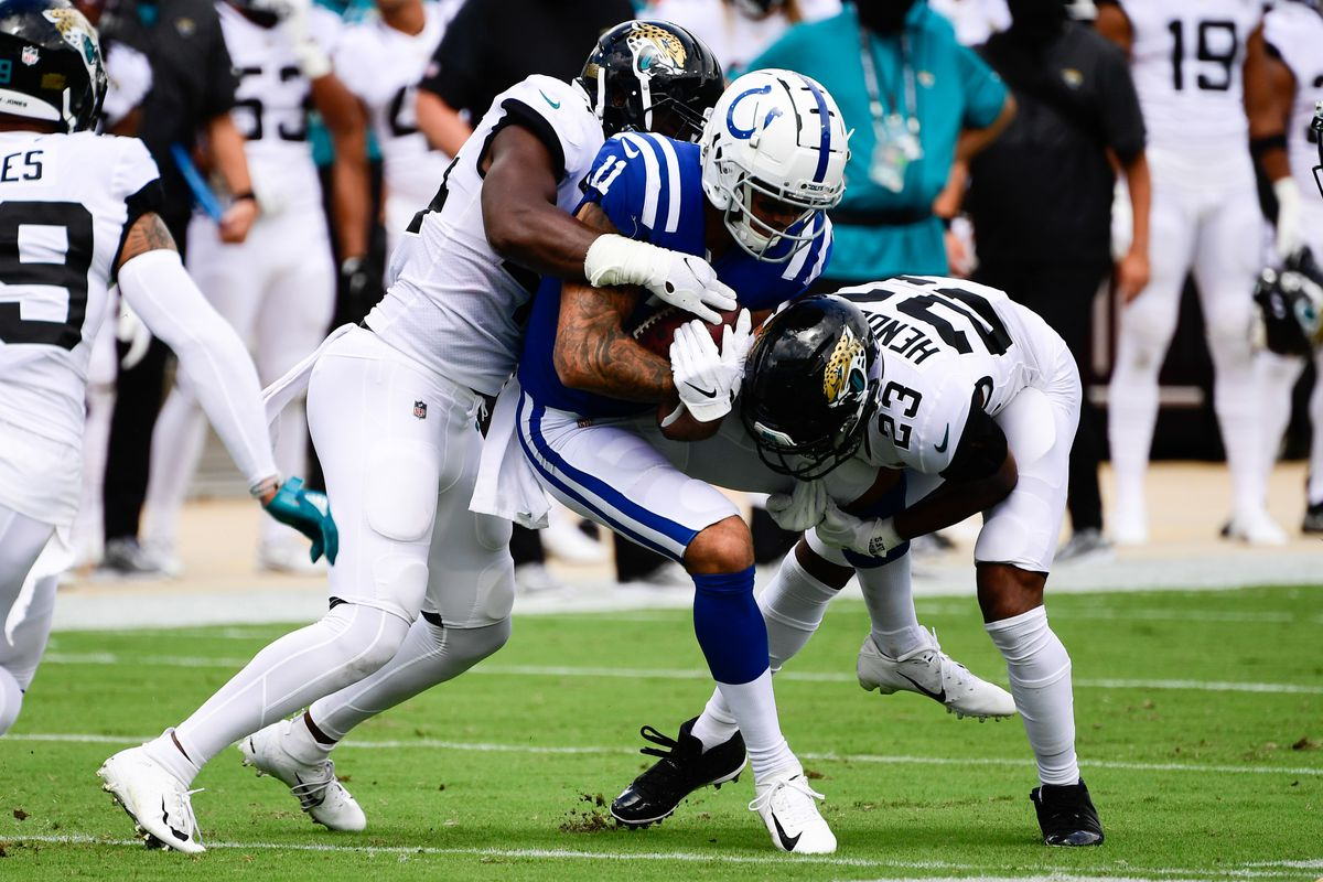 Indianapolis Colts wide receiver Michael Pittman Jr. (11) is tackled by Jacksonville Jaguars cornerback CJ Henderson (23) and linebacker Myles Jack (44) during the first quarter at TIAA Bank Field. Mandatory Credit: Douglas DeFelice
