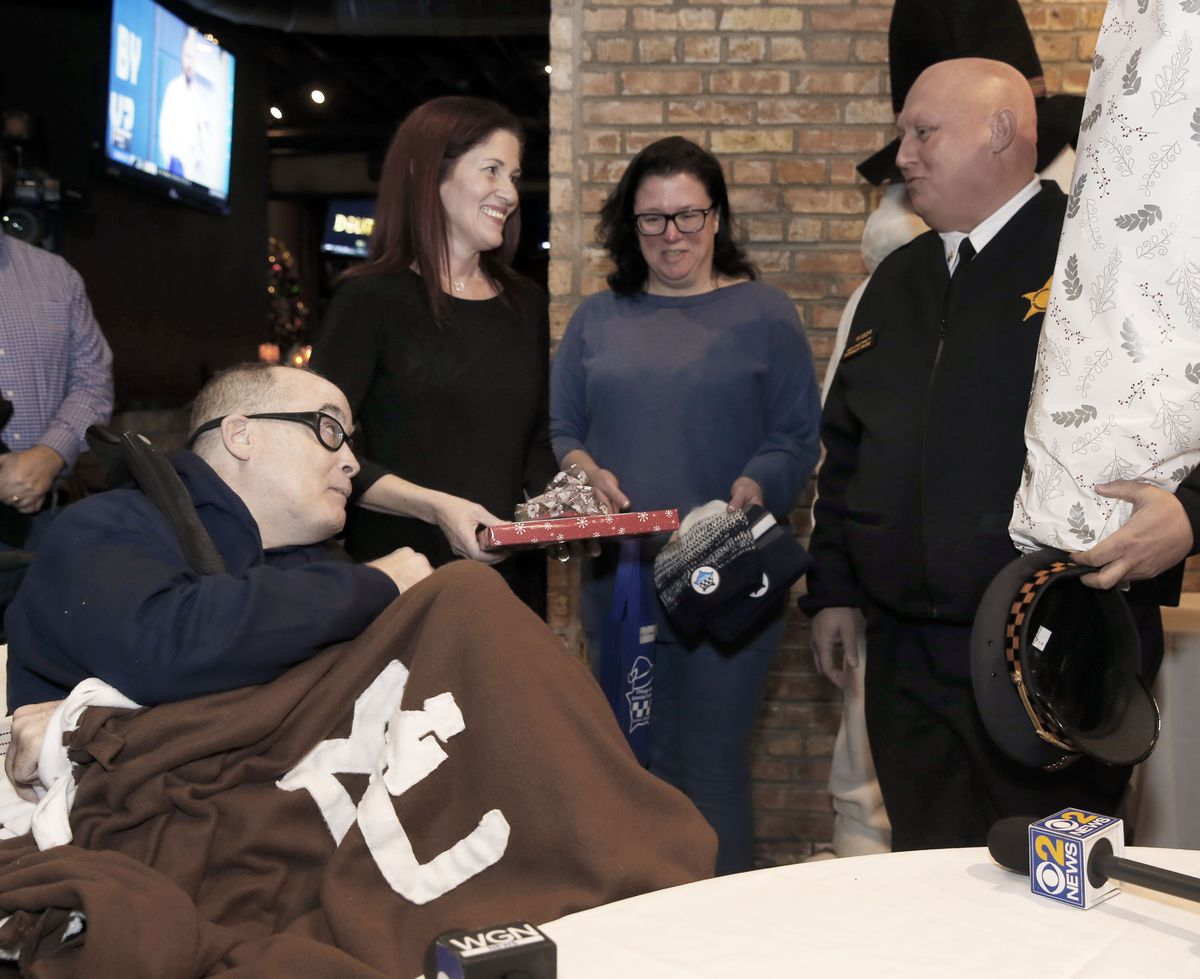 Commander Rick Wiser, right, presents former CPD officer Jim Crowley with a welcome home Christmas gift as Crowley's sister, Beth Carter and Dawn Dolan, of the police memorial foundation look on in Chicago, Monday, December 23, 2019.