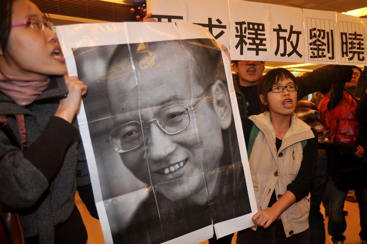 Two women hold a black and white portrait of Liu Xiaobo