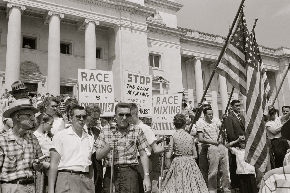 People holding signs and American flags protesting the admission of the 'Little Rock Nine' to Central High School, 1959.