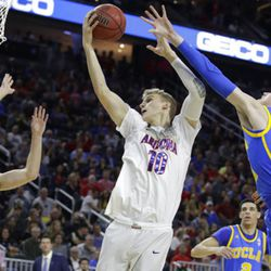 Arizona's Lauri Markkanen, center, grabs a rebound between UCLA's Bryce Alford, left, and TJ Leaf, right, during the first half of an NCAA college basketball game in the semifinals of the Pac-12 men's tournament Friday, March 10, 2017, in Las Vegas.