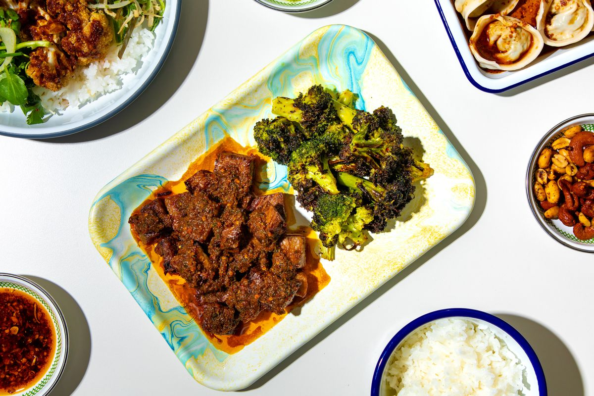 Cubes of brown Yunnan-style brisket on a rectangular plate sit next to a pile of bright green broccoli
