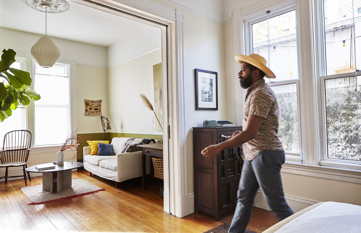George walking from his bedroom to the living room; the rooms are connected with just one large door opening between them, and a pocket door that can close off the bedroom.