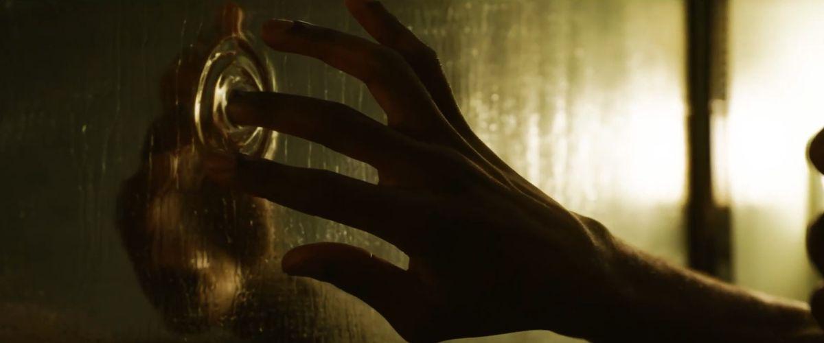 yahya abdul-mateen ii's hand touches a liquid mirror in The Matrix Resurrections