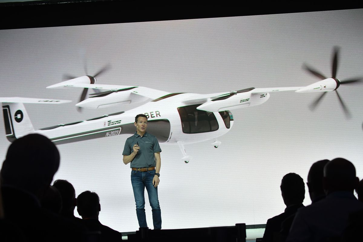 """Jeff Holden, Uber chief product officer, speaks onstage in front of a picture of a """"flying taxi"""""""