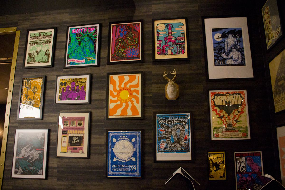 Varying colorful concert photos and a taxidermied jackalope mount on a dark wooden wall