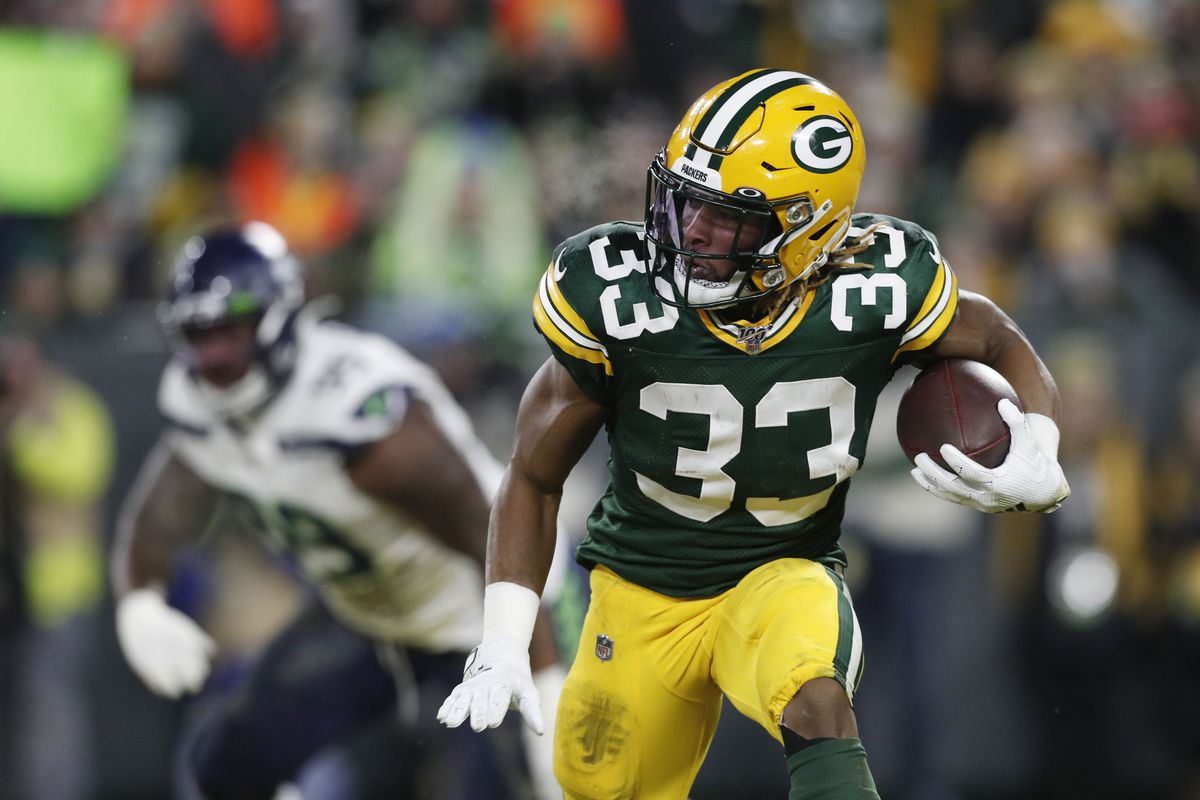 Green Bay Packers running back Aaron Jones runs the ball against the Seattle Seahawks in the first quarter of a NFC Divisional Round playoff football game at Lambeau Field.
