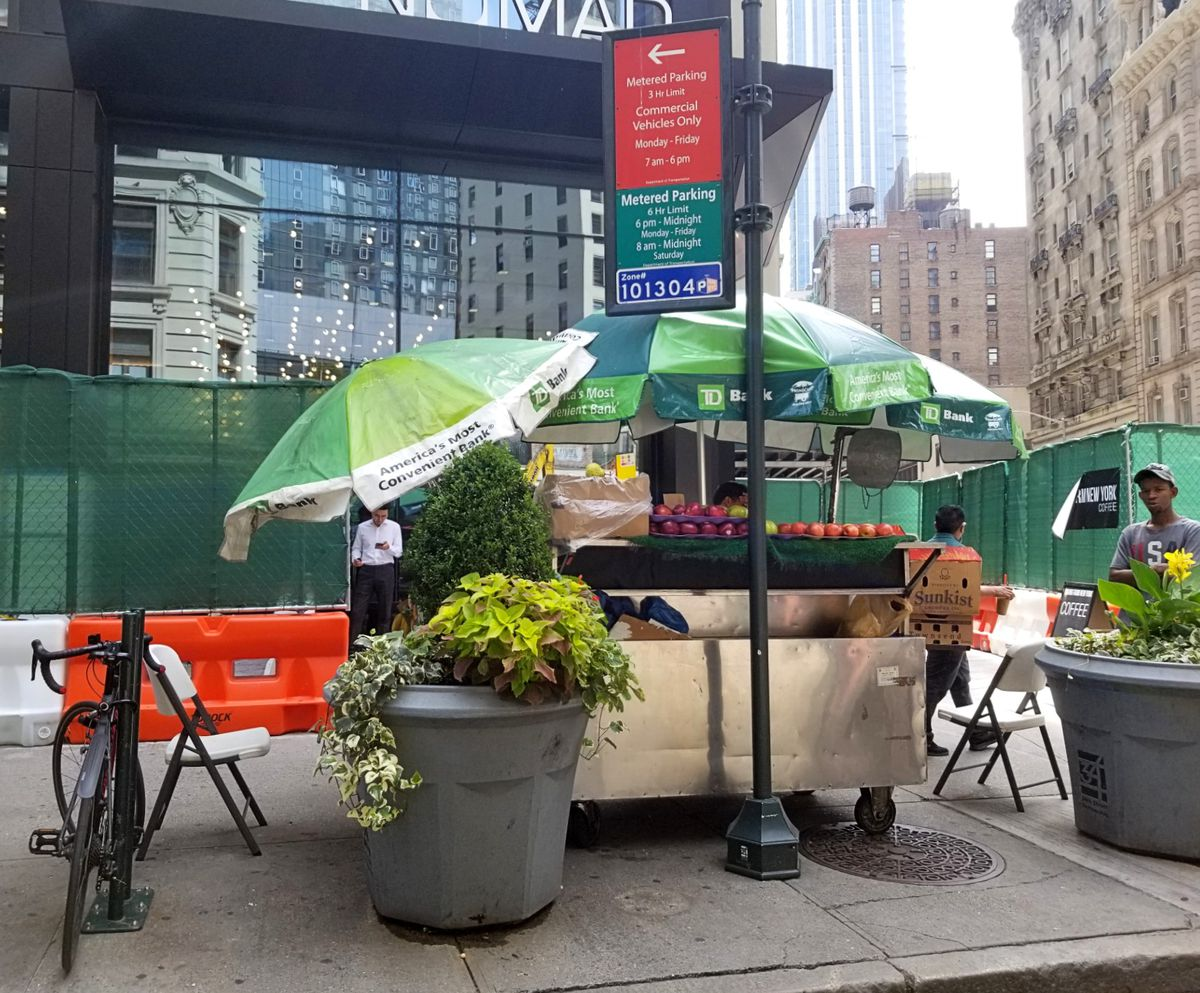 A fruit stand with three green and white umbrellas shielding the fruit from the sun. A recently installed stone planter, bike rack, and way-finding sign are directly in front of the cart on the curb.