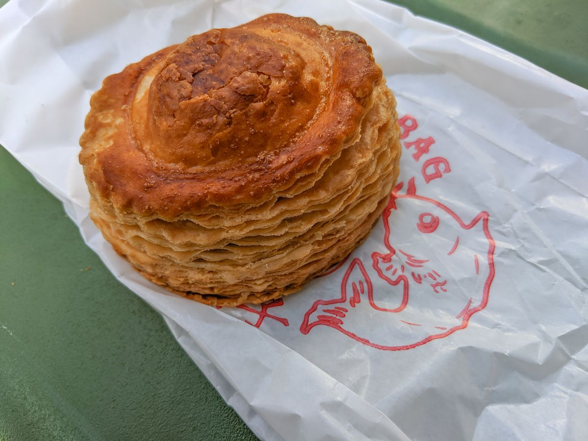 """A flaky, golden puff pastry sits on a white bag, with the word """"Bag"""" and a fish visible in red. The bag sits on a green table."""