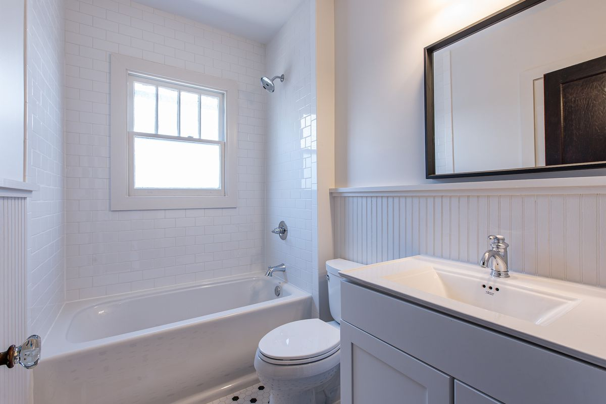 White bathroom with single vanity, framed mirror, and tiled shower with window.