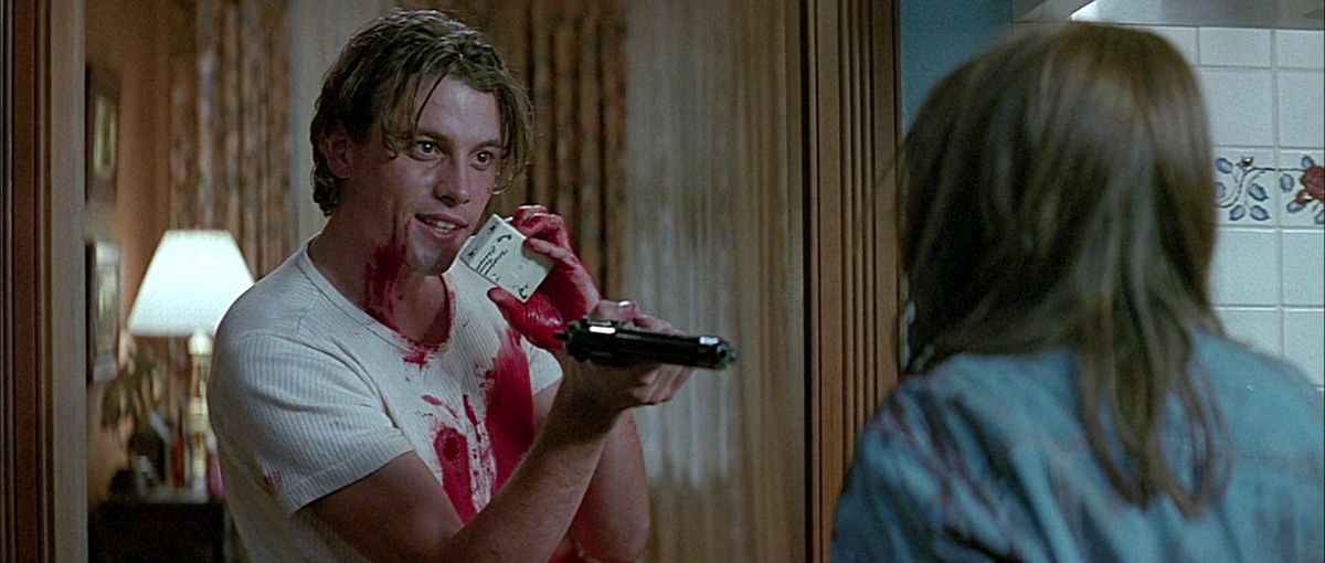 billy loomis (skeet ulrich) stands in sidney's kitchen with a bloody white t-shirt holding her at gunpoint and talking through the ghostface voice box