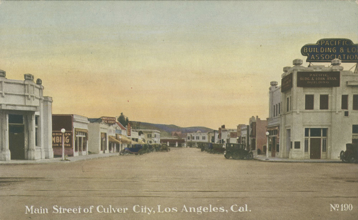 A colored postcard of a small downtown with a main street and low hills and a sunset in the background.