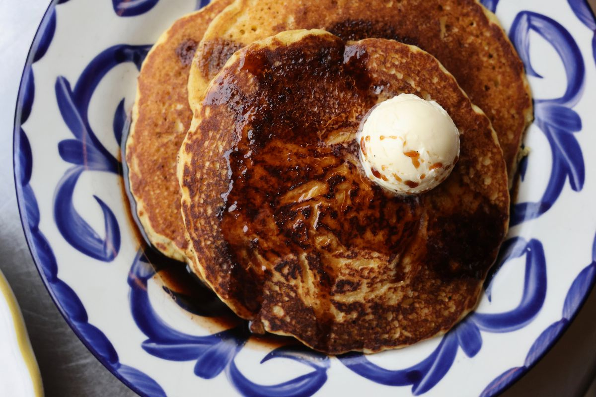 Three pancakes on a plate covered in syrup and a scoop of whipped butter