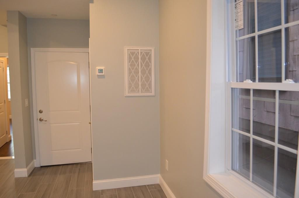 A condo's entry hall with a thermostat on the wall, and the view is of facing the closed front door.