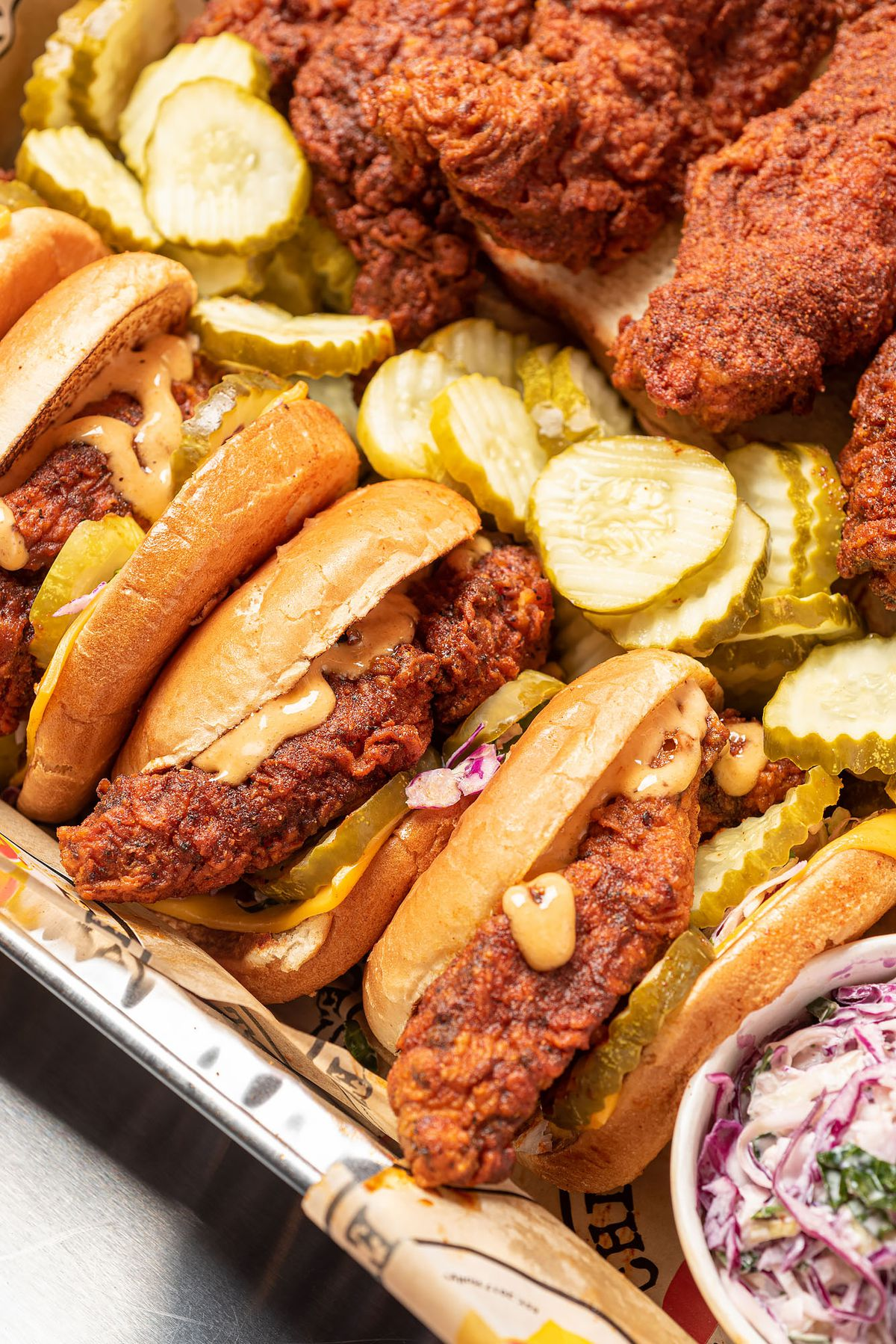 A packed tray with chicken tender sliders, pickles, and lots of sauce.