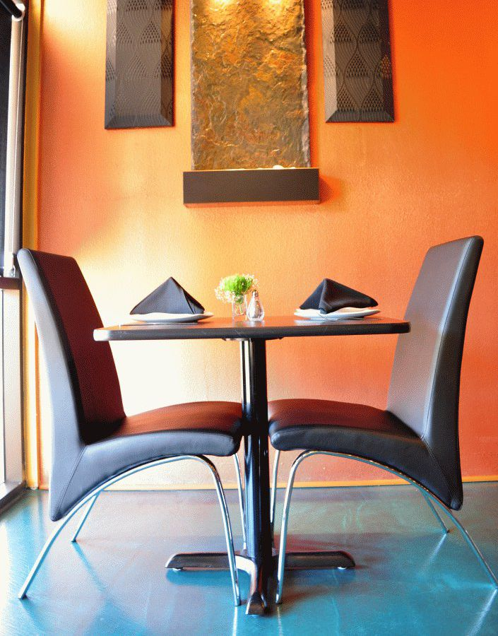 A table with two black chairs and an orange wall