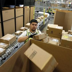 FILE - In this Nov. 11, 2010 file photo, Ricardo Sandoval places packages in the right shipping boxes at an Amazon.com fulfillment center, in Phoenix. Products are flying off the shelves at Amazon warehouses across the county as Californians prepare to start paying sales taxes on online purchases. The change, which takes effect Saturday, Sept. 15, 2012, will pave the way for the e-commerce giant to open warehouses in California and offer same-day shipping to customers.
