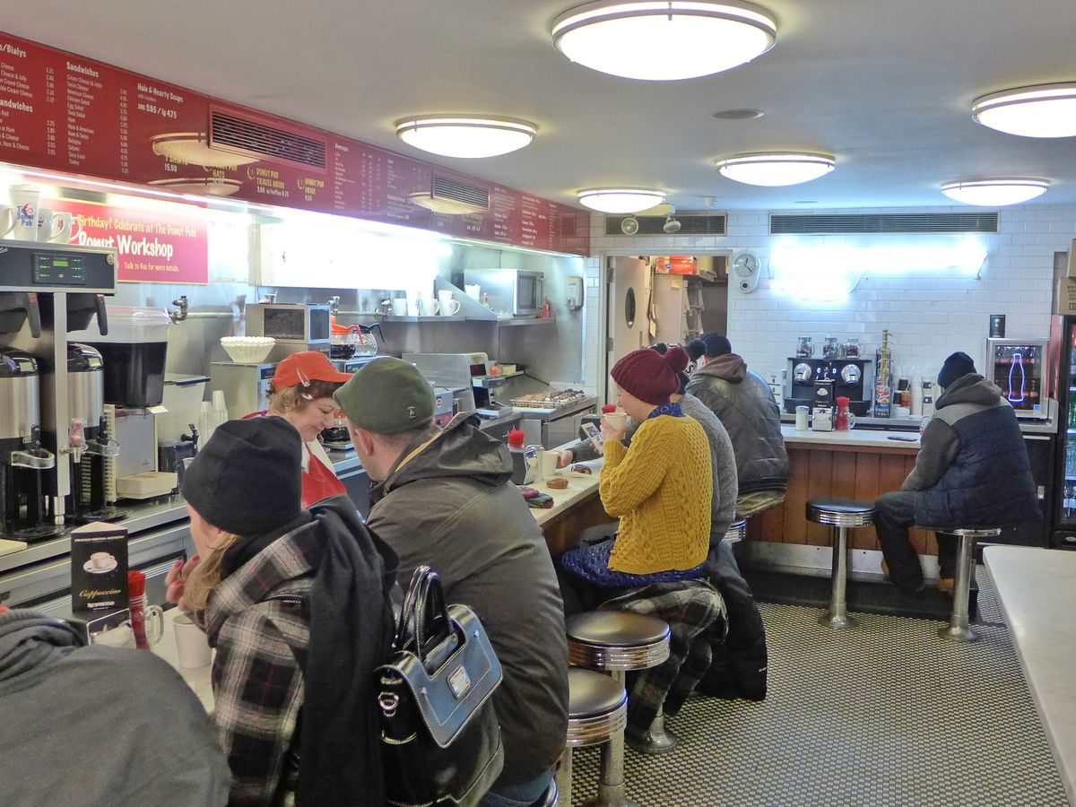 A number of snow capped figures sit at an L shaped lunch counter.