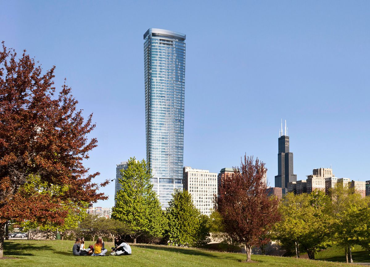 In the foreground is a park with trees and grass. In the background is a city skyline with buildings of varying heights including one tall skyscraper.