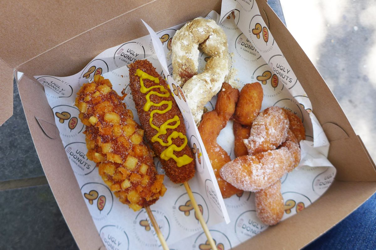 A box with imprinted tissue inside, battered franks on a stick at the left, and three twisted doughnuts on the right.