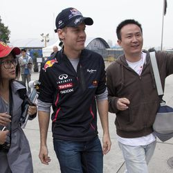 Red Bull Formula One driver Sebastian Vettel, second right, of Germany is photographed with fans as he walks through the F1 paddock at the Chinese Formula One Grand Prix in Shanghai, China, Thursday, April 12, 2012.
