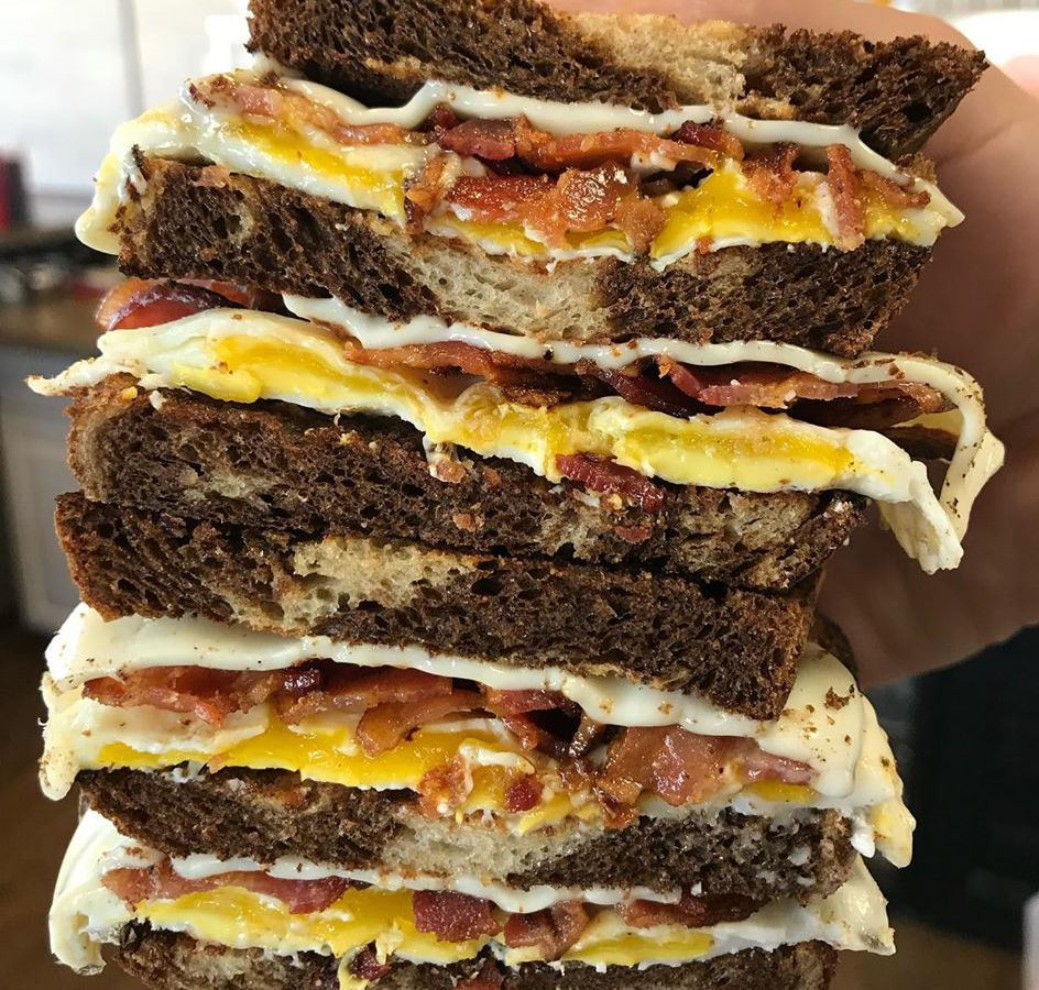 Close up on a bacon, egg, and cheese sandwich on marble rye, held in someone's hand