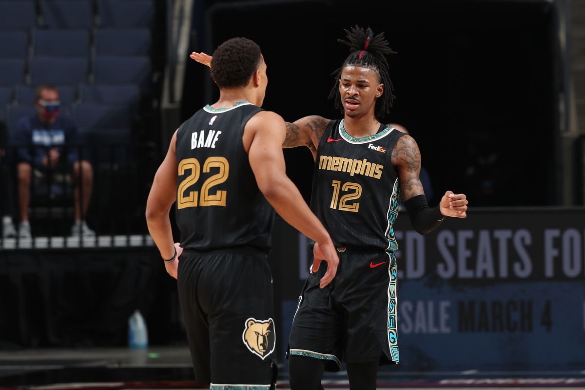Ja Morant hi-fives Desmond Bane of the Memphis Grizzlies during the game against the LA Clippers on February 26, 2021 at FedExForum in Memphis, Tennessee.