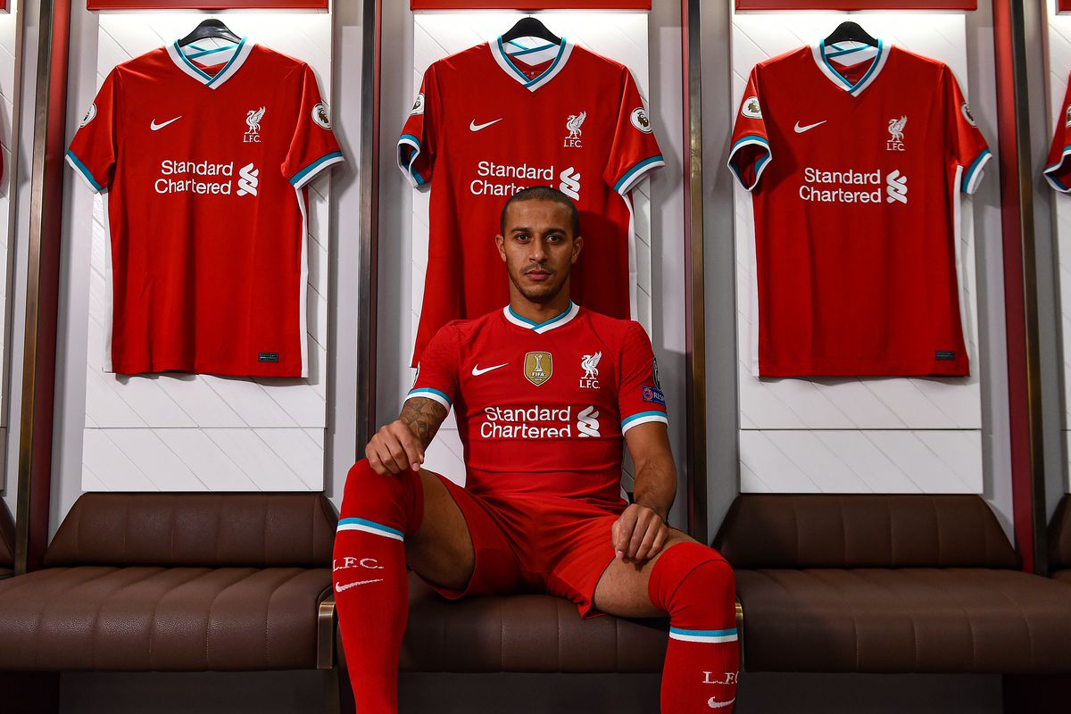 Liverpool Unveil New Signing Thiago Alcantara, pictured here sat in the Anfield dressing room in the 2020/21 home kit, looking intimidating at the camera