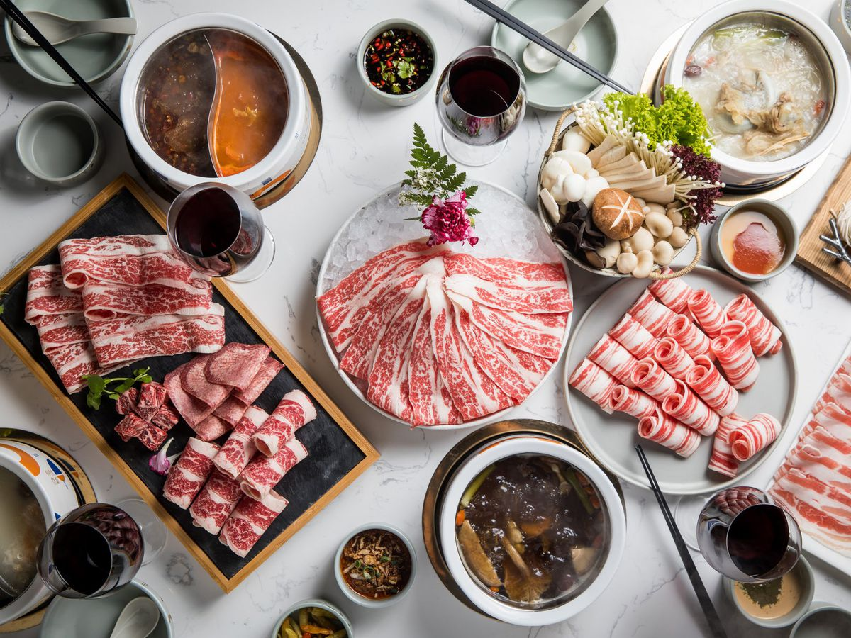 From above, a table spread with large trays of arrayed cuts of beef, baskets of raw vegetables, and bubbling soups