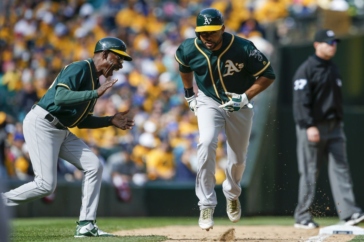 Oakland A's third base coach Ron Washington celebrates Coco Crisp hitting a home run in Sunday's contest against the Seattle Mariners.