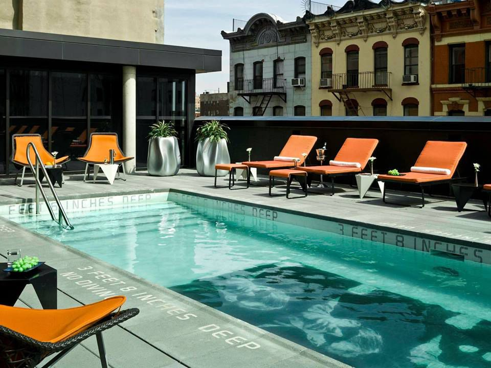 A set of a half-dozen orange reclining chairs sits beside a clear pool