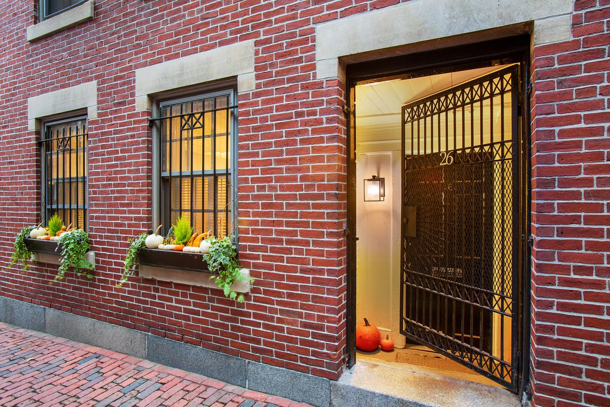 The brick exterior of an apartment building ,with a partially opened wrought-iron door.