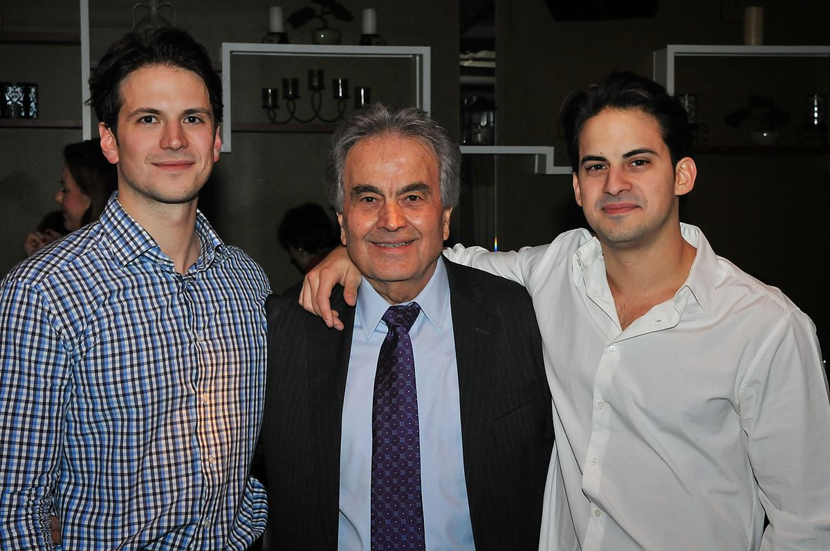 Three men standing in a line posing together and looking at the camera