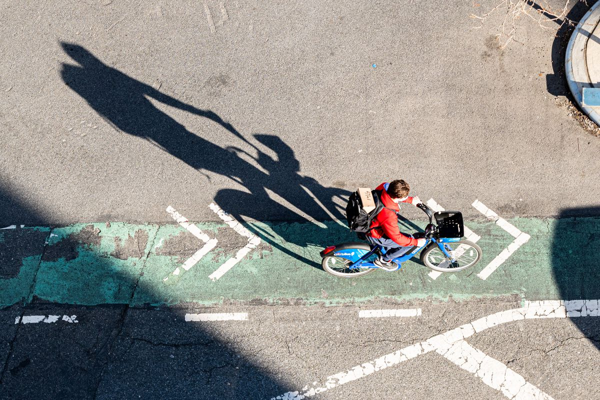 A person on a bike, seen from above, pedals along a green-painted strip on a cement road.