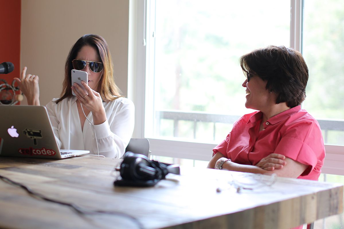 Lauren Goode, left, imitates Kara Swisher, right, by wearing Ray-Ban sunglasses and holding an iPhone up to her face.