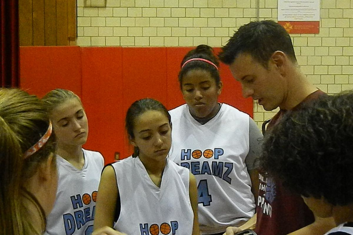 Coach Billy Armstrong with his Hoop Dream girls tuned in to his every word.