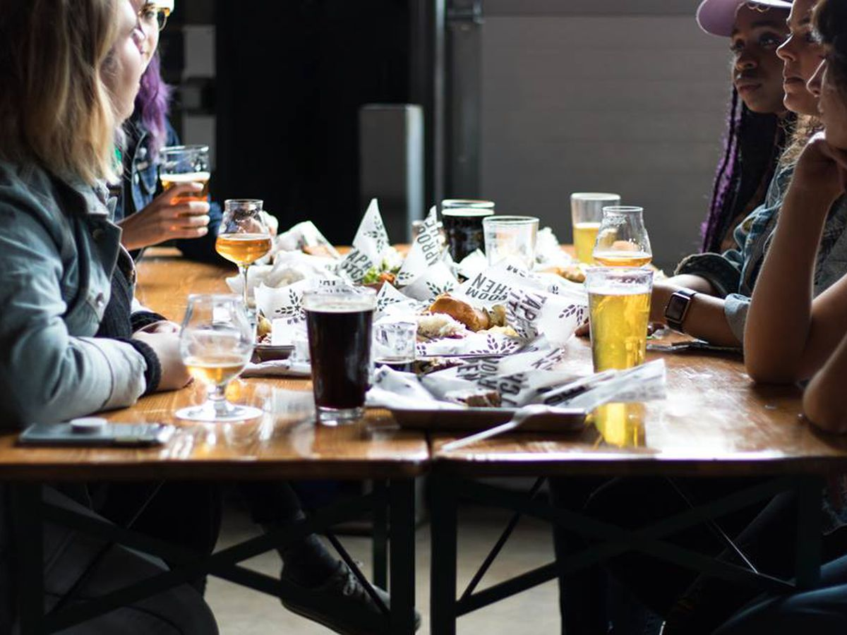 Several people gathered around a table filled with trays of food in plastic boats and beers.